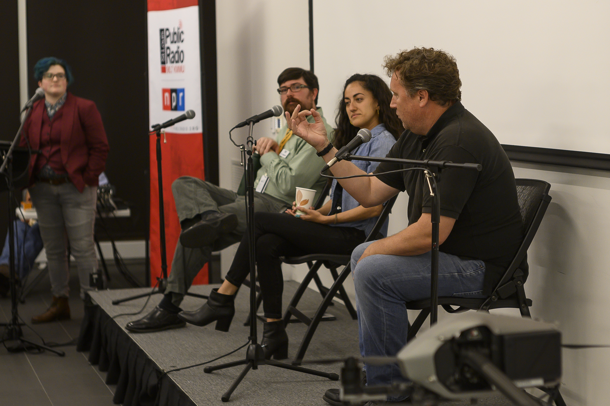 Speaker David Carson makes a hand gesture. Visible are Host Kae Petrin, and speakers Brent Jones and Carolina Hidalgo