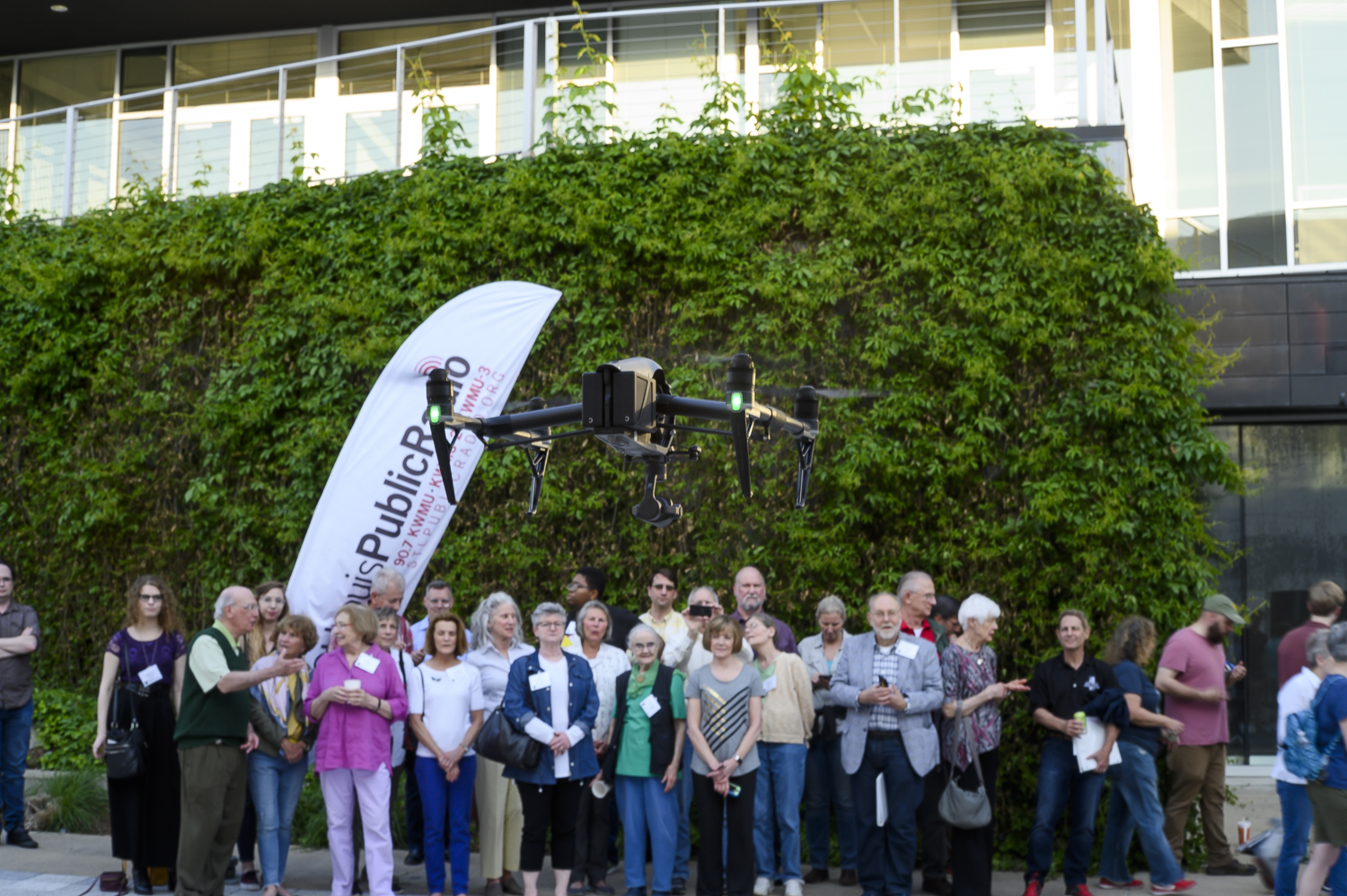 A drone flies in the middle of the photo. Attendees can be seen watching it.