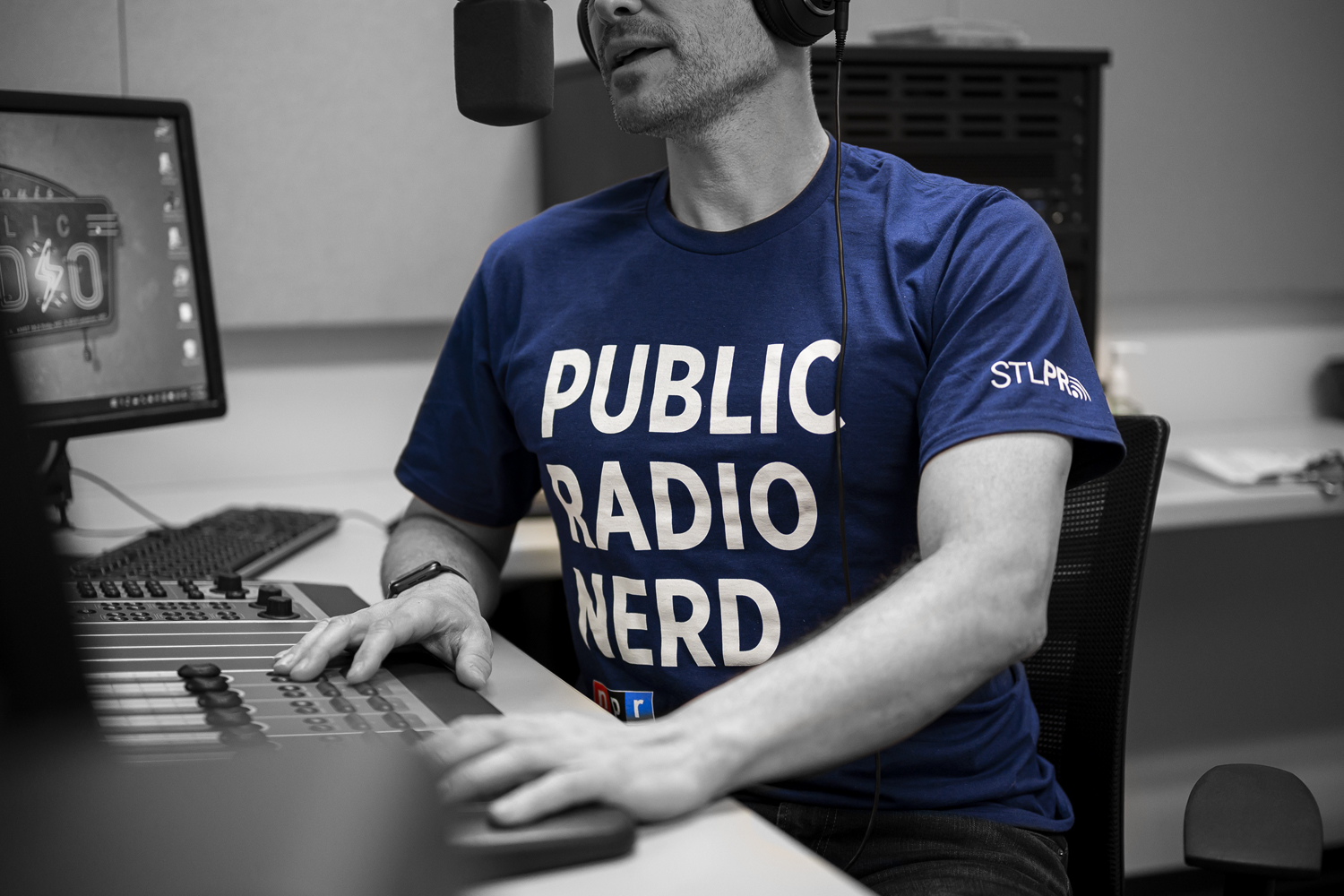 A man speaks into a microphone, his hands on a soundboard. His shirt reads 'Public Radio Nerd'