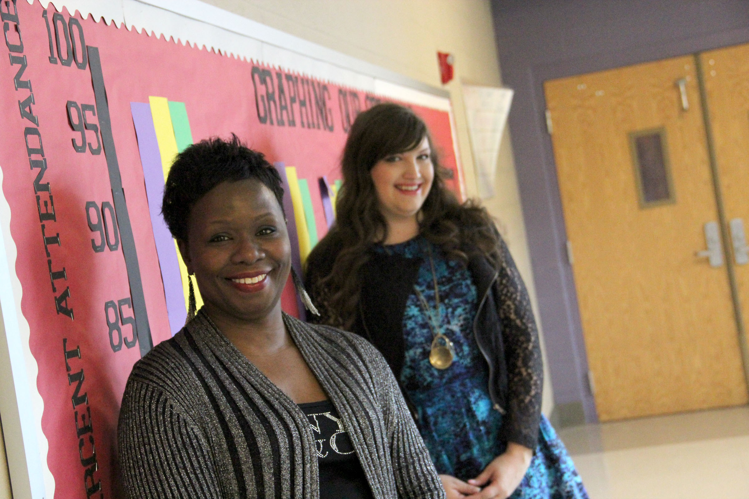 Westview Middle School Principal Valeska Hill and sixth grade math teacher Melissa Schut stand next to a bulletin board showing month attendance at the school.